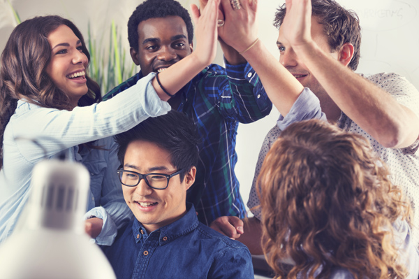 Multi cultural group of young business people celebrating success. Everyone is looking at a ecstatic smiling or laughing and happy. Group high five. Asian, African and Caucasian ethnic backgrounds